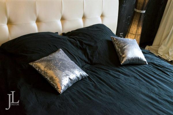 Белые шторы и подушки в спальне.